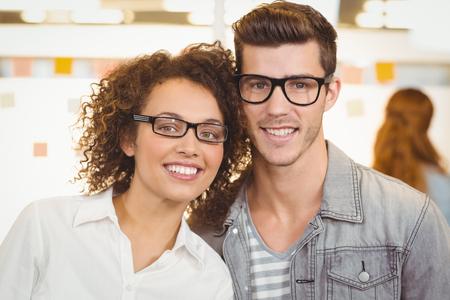 hombres guapos: Retrato de gente sonriente de negocios que usan gafas en la oficina creativa