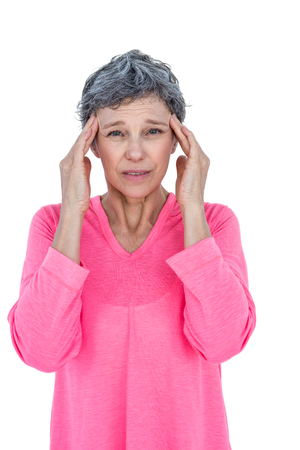 wincing: Portrait of mature woman suffering from headache against white background