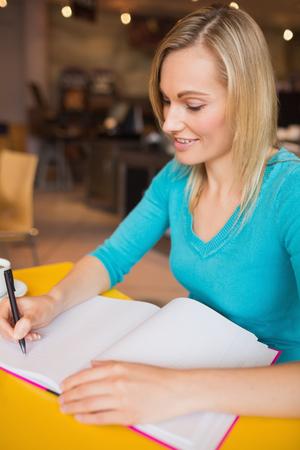 persona escribiendo: Primer plano de la escritura feliz mujer joven en el libro en la mesa de café Foto de archivo