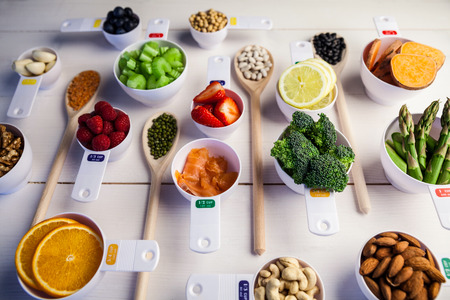 lima bean: Portion cups and spoons of healthy ingredients on wooden table