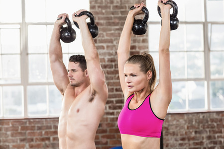 lean out: muscular serious couple with kettlebells in crossfit gym