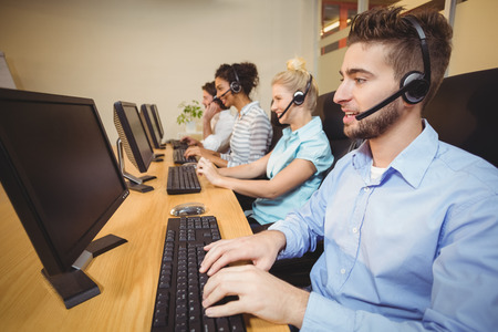 call center office: Executives working in call center wearing headsets