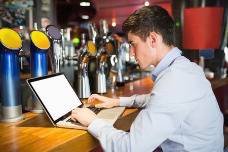 bar counter: Side view of man using laptop at bar counter Stock Photo