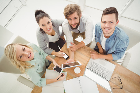 coworker: Overhead portrait of smiling business people while sitting at desk