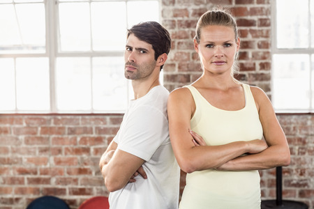 exercise room: Portrait of a fit young couple standing with arms crossed in a bright exercise room