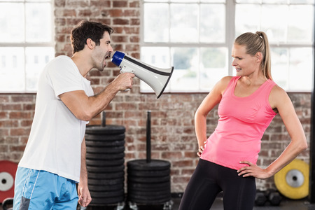 motivating: Personal trainor motivating his client with megaphone in crossfit gym Stock Photo