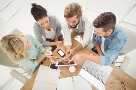 Overhead view of business people with digital tablet while sitting at desk Standard-Bild
