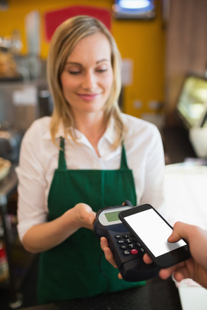 accepting: Female worker accepting payment from customer through NFC in bakery Stock Photo