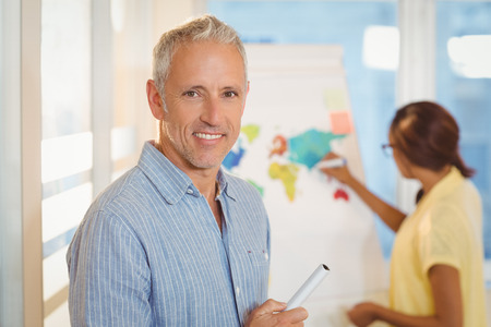 casual business man: Portrait of smiling businessman standing against female colleague working in meeting room at creative office