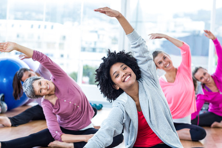 Cheerful women exercising with arms raised in fitness studio Imagens