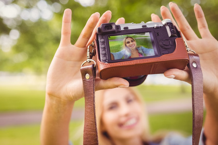self   portrait: Smiling woman taking self portrait with camera while standing in park