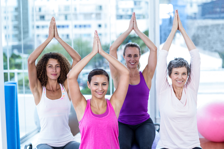 joined: High angle portrait of smiling women with joined hands in fitness studio