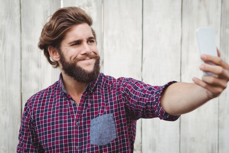 making face: Hipster making face while taking selfie against wooden fence Stock Photo