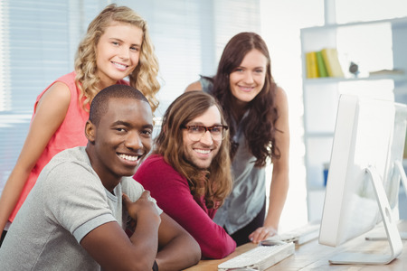 team work: Portrait of smiling business team working at computer desk in creative office Stock Photo