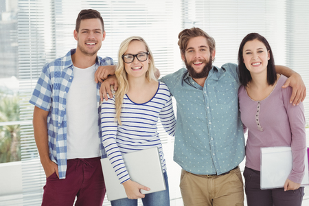 arm around: Portrait of smiling business people with arm around while standing at office Stock Photo