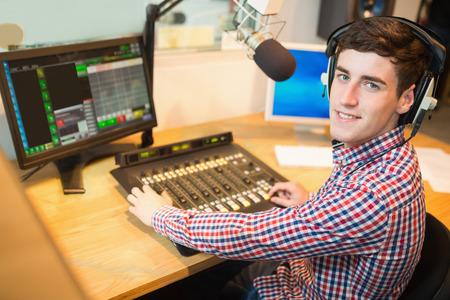 microfono de radio: Retrato de locutor de radio que operan mezclador de sonido en la mesa en el estudio