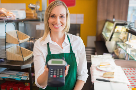 bakery store: Portrait of happy female shop owner holding credit card reader in bakery Stock Photo