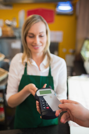 accepting: Female worker accepting payment from customer through credit card in bakery