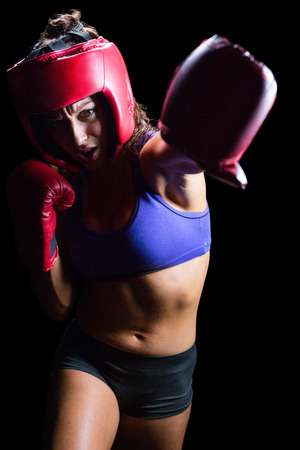 headgear: Female boxer with gloves and headgear punching against black background