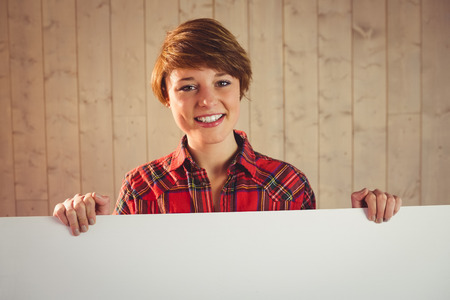 woman holding sign: Pretty young woman holding sign on wooden planks background