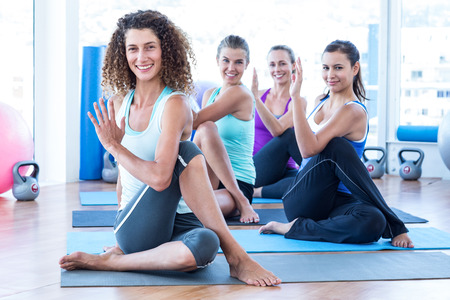 spine: Portrait of cheerful women doing spine twisting pose on exercise mat