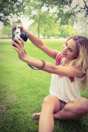self   portrait: Happy woman taking self portrait with camera while sitting on grass in park