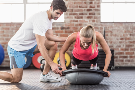 push ups: Trainer motivating client doing push ups in crossfit gym