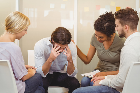consoling: Business people consoling businessman suffering from headache in office
