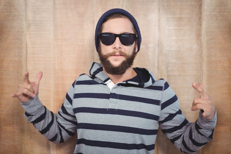 hand sign: Hipster showing rock and roll hand sign against wooden wall Stockfoto