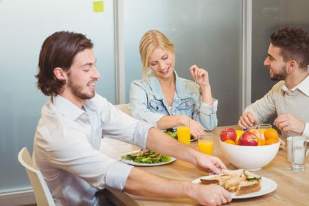 to lunch: Empresario plato de s�ndwich como colegas hablando entre s� la celebraci�n durante el almuerzo en la oficina creativa