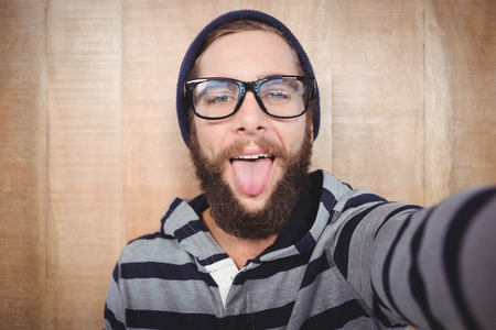 sticking out tongue: Portrait of happy hipster sticking out tongue against wooden wall