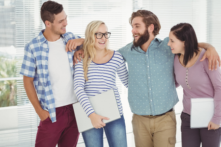 arm around: Smiling business people with arm around while standing at office Stock Photo