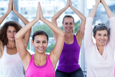 joined hands: Portrait of smiling women with joined hands in fitness studio Stock Photo