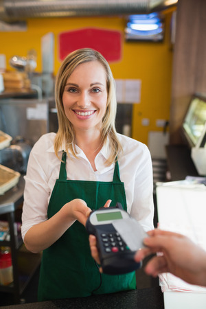 accepting: Portrait of female worker accepting payment from customer through credit card in bakery Stock Photo