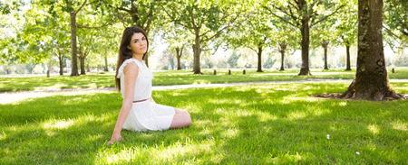 people   lifestyle: Panoramic view of park while young woman sitting on grassland Stock Photo