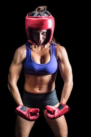 female boxer: Portrait of female boxer flexing muscles against black background