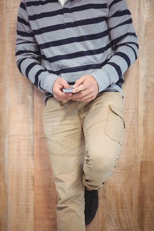 low section: Low section of man using smartphone leaning against wooden wall Stock Photo