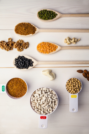 lima bean: Spoons and cups of pulses and seeds on wooden table