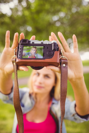 self   portrait: Woman taking self portrait with camera while standing in park
