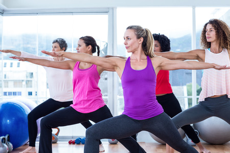 Women exercising with arms outstretched in fitness studio Stock Photo
