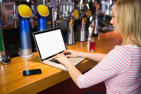 side bar: Side view of woman working on laptop at bar counter