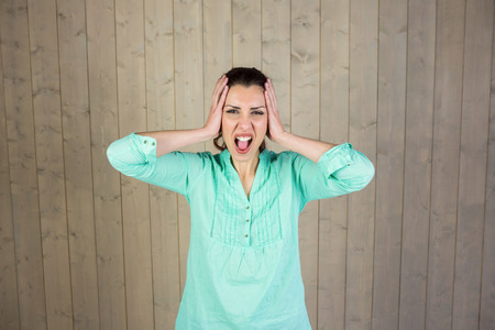 screaming head: Portrait of woman screaming with head in hands at home Stock Photo