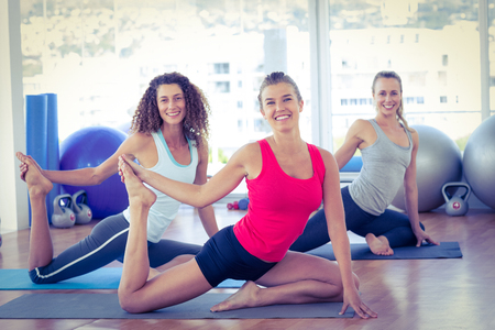 grab: Portrait of happy women doing pigeon pose with one hand right leg grab Stock Photo