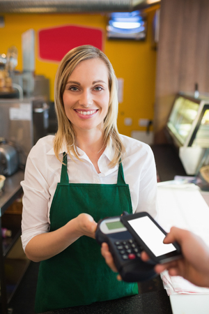 accepting: Portrairt of female worker accepting payment from customer through NFC in bakery Stock Photo