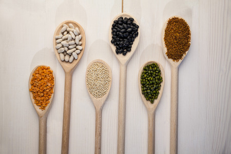 pulses: Wooden spoons of pulses and seeds on wooden table Stock Photo