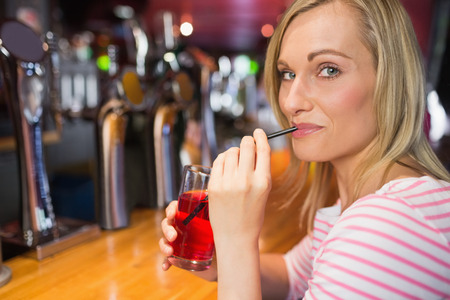 sipping: Portrait of young woman sipping drink at bar counter Stock Photo