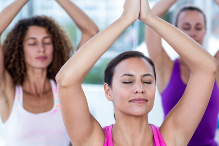 manos unidas: Women meditating with joined hands and arms raised in fitness studio Foto de archivo