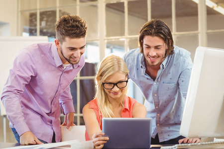 personas mirando: Smiling business people looking at digital table in office