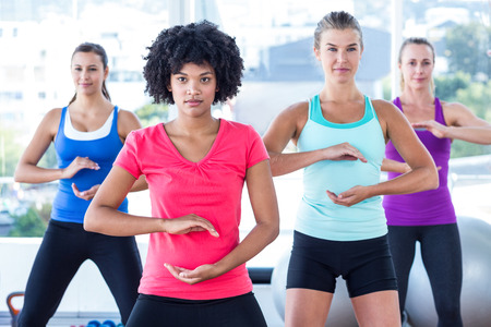 fit women: Fit women exercising with trainer at fitness studio Stock Photo