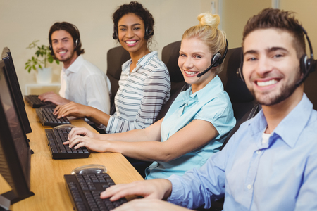 center agent: Portrait of smiling executives working together in call center